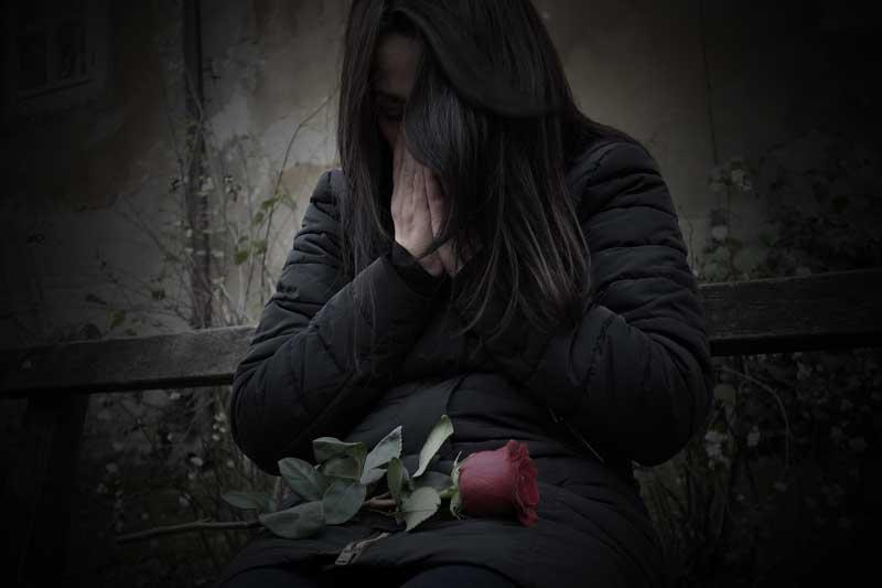 Mujer llorando con flor, por cibervenganza al hacer sexting