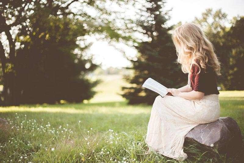 Niña leyendo un libro al aire libre